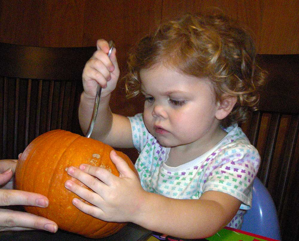pumpkin carving how-to, little girl scooping out a pumpkin