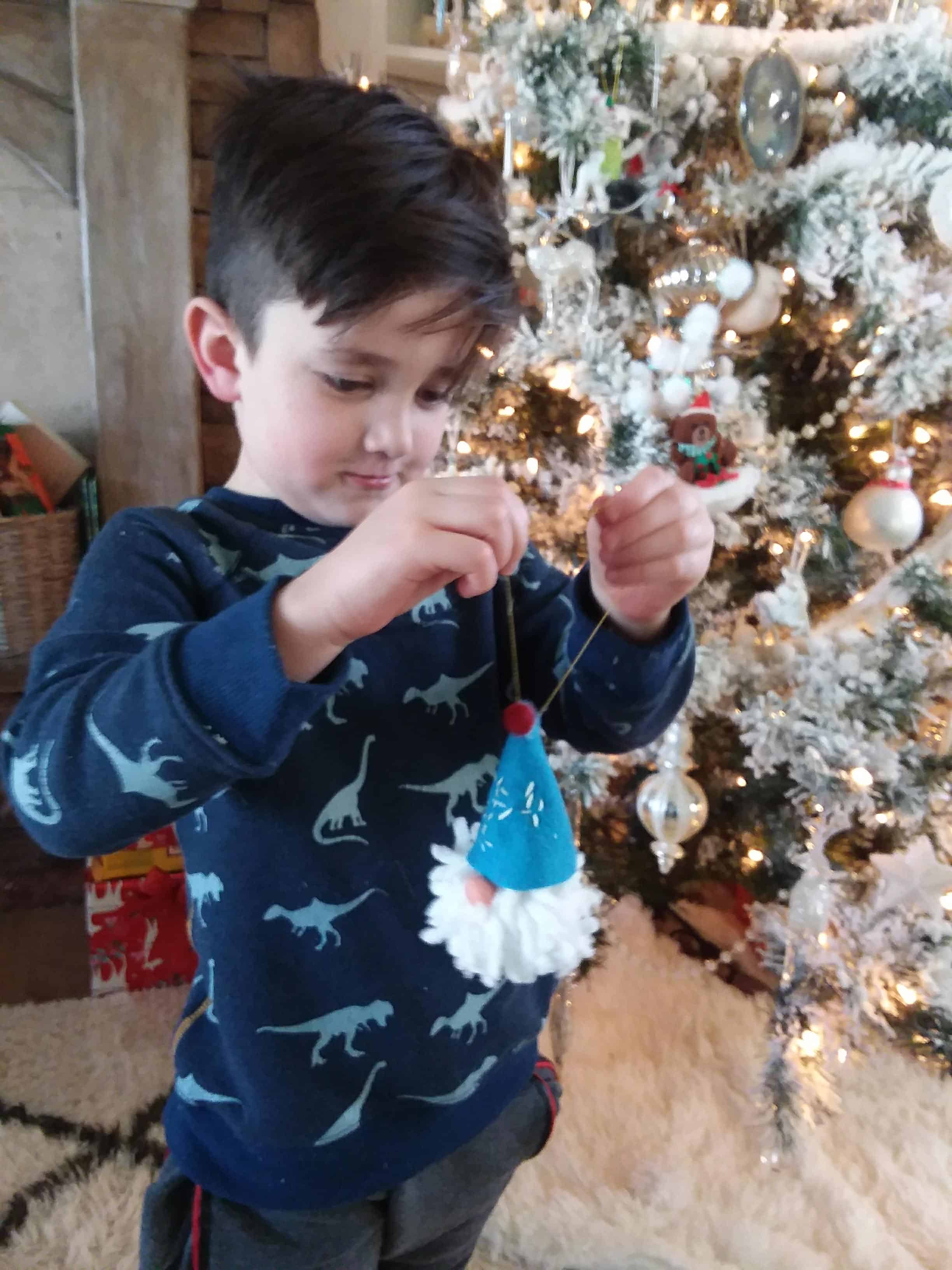 grandparent activities: little boy decorating the Christmas tree with handmade ornament