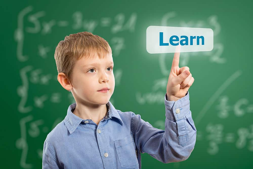"boy pointing to a chalk board with the word, ""learn"""